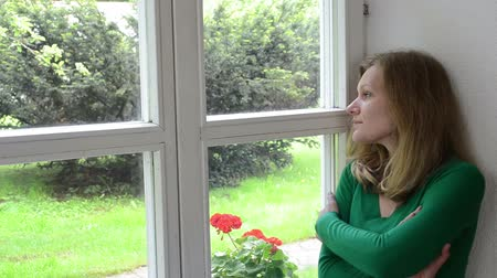 headshrinker : sad shrinked woman sits on window sill and look far away. Stock Footage