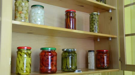 conservado : woman puts jars with pickled red peppers and tomatoes in a kitchen cupboard shelves