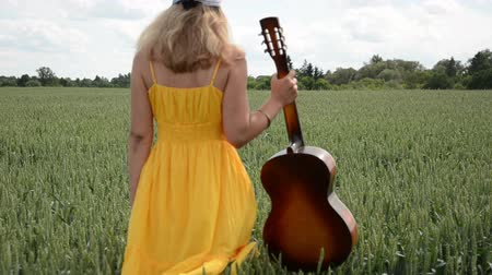 singers : young musician with guitar in hand walks dreamily swaying corn fields in summer day