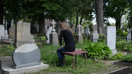могила : Young woman sit on bench near father grave in cemetery. Deppresed girl in graveyard.