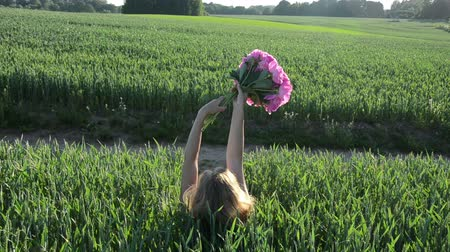 mavi arka : blonde woman lies down between the green young corn with a bouquet of peonies hands back view