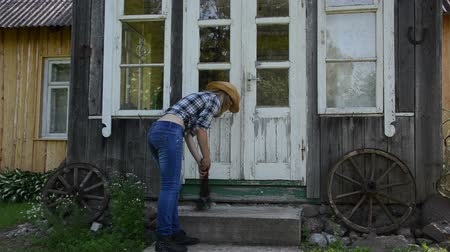 besom : Worker girl in shirt jeans and hat clean sweep stairs with wooden broom in rural homestead yard. Stock Footage