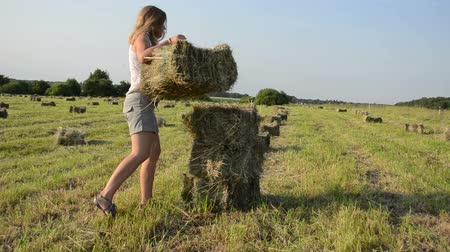 farmer animals : Attractive young farmer woman girl dressed in shorts carry stack bales of hay.