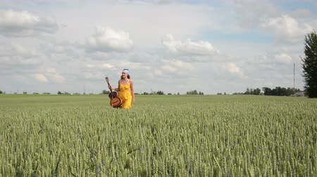 hippie : pretty woman in yellow dress and headscarf walk in wheat field with guitar posing. Stock Footage