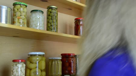 conservado : blonde girl puts jars of canned cucumbers and peppers in a wooden cupboard Vídeos
