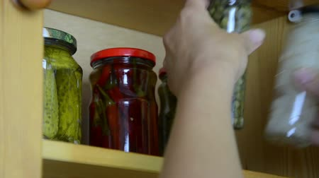 kırsal : hand put small jars on the shelf next to other pickled vegetables in glass jars