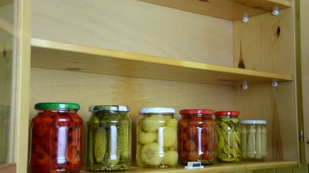 conservado : girl opens a cupboard door and puts different sized jars of pickled and preserved vegetables