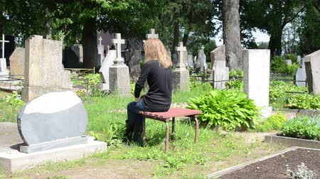 temető : Depressed woman mourn near husband grave in cemetery. Deppresed girl in graveyard. Stock mozgókép