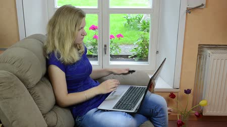 cellphone : Pretty business woman work with laptop notebook computer and answer talk with smart phone sitting on armchair near window. Stock Footage