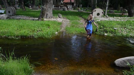 in : young girl holds a dress skirt and wade barefoot pebble creek sunny summer day