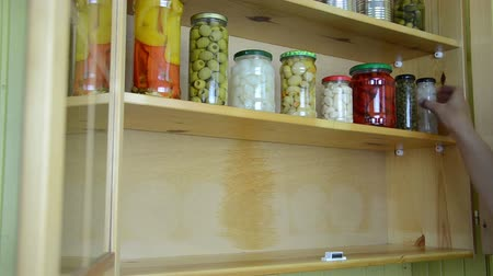 conservado : girl hand opens a wooden cupboards door and take all the jars from the shelf Vídeos