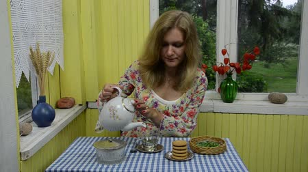 smell : Woman mix herbal mint balm leaf tea in retro cup and drink it. Herbal alternative medicine. Rural house veranda decorations.