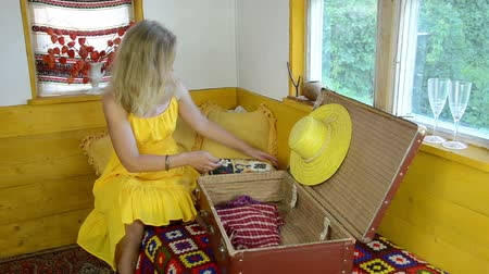 brown dress : blonde woman with yellow summer dress put summer clothes and a straw hat on old leather suitcase Stock Footage