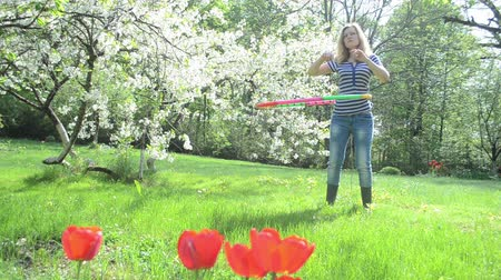 ботинок : woman spin turn colorful hula hoop colorful ring on waist and back near beautiful blossom fruit tree and tulips. Стоковые видеозаписи