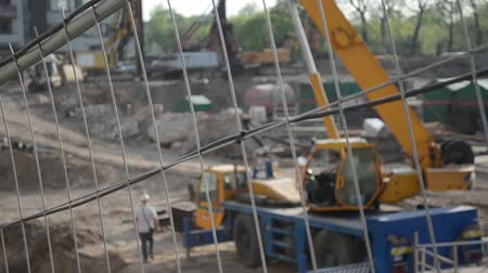 maquinaria : Fast speed up view construction site fence and blur people work with heavy machinery equipment. Vídeos
