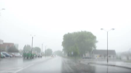 fall through : auto cars drive on urban town city road and rain fall. Front automobile window windscreen view and wipers work. Bad weather conditions in autumn.