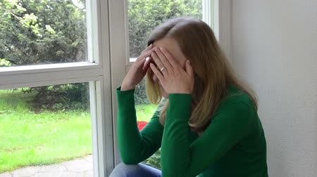 headshrinker : sad worried crouched woman sits on window sill.
