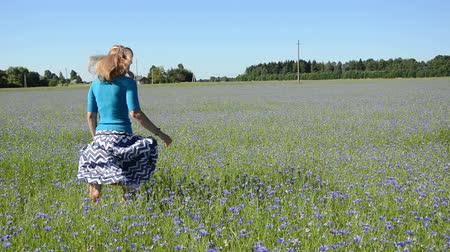 луг : young woman with a summer skirt and blue blouse fun running through the cornflower meadow in summer day Стоковые видеозаписи