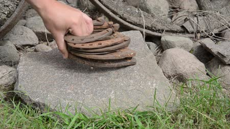 ranč : Hand put stack of retro rusty horse shoes on big stone. Dostupné videozáznamy