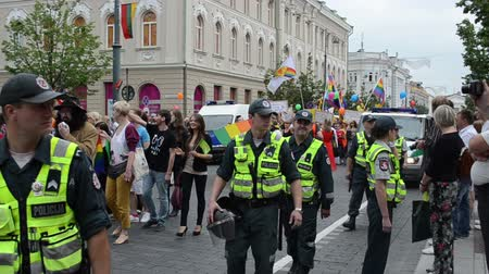 participante : VILNIUS, LITHUANIA - JULY 27: huge policeman force protect loudly gay parade participants with balloons and flags in public street event on July 27, 2013 in Vilnius, Lithuania. Vídeos
