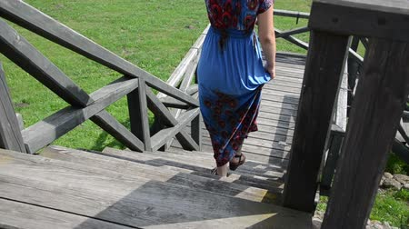 parke taşı : blonde woman with blue flowered dress climbs the old wide wooden stairs Stok Video