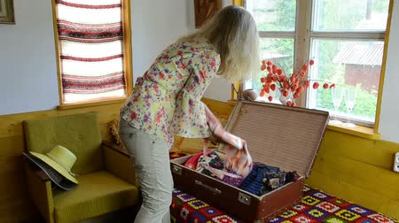 levou : big brown antique suitcase lying open on the bed rural women take summer blouses