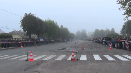slalom : SIRVINTOS, LITHUANIA - SEPTEMBER 29: slalom race in town with a group of viewers foggy afternoon. Car rides slalom race manoeuvre between the red tower  on September 29, 2013 in Sirvintos, Lithuania.