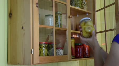 conservado : girl from kitchen cupboards take and inspect a jar of canned green tomato