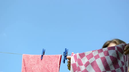 varal : Long haired woman hang clothes to dry on clothes line rope after laundry on background of blue sky. Vídeos