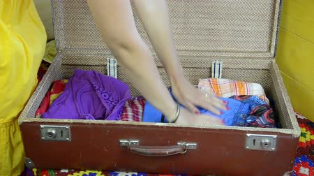 dava : woman hands with red polished nails folds blue long dress and closes the suitcase