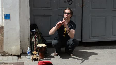 woodwind : VILNIUS, LITHUANIA - MAY 18: Man play with flute fife pipe in oldtown street free event and people pass on May 18, 2013 in Vilnius, Lithuania. Street music day.