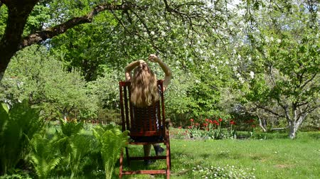 yards : Woman relax sitting on wooden chair in spring garden near fern and blooming apple tree. Stock Footage