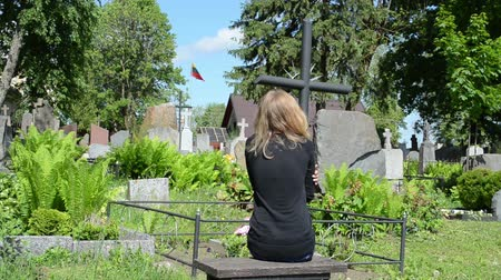 могила : Sad woman sit near father grave in cemetery. Patriot soldier died. National Lithuania flag.