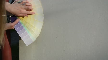 decorador : Hands with color scale palette trying to match select exact color of outdoor building house wall.
