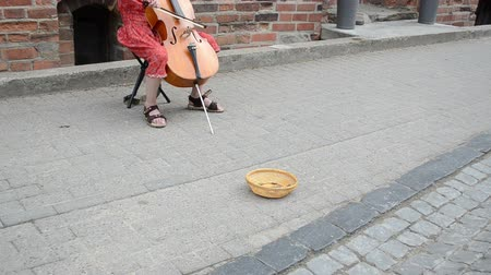 lower part : VILNIUS, LITHUANIA - MAY 18: girl lower body part play with cello violoncello in oldtown street music day and wicker dish for money on May 18, 2013 in Vilnius, Lithuania.