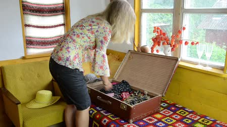 шорты : Blond woman girl unpack her clothes into retro travel portmanteau suitcase.