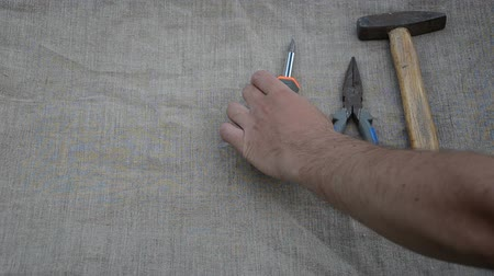 opravář : Man hand put hammer pliers screwdriver tape-measure knife tools on linen material surface.