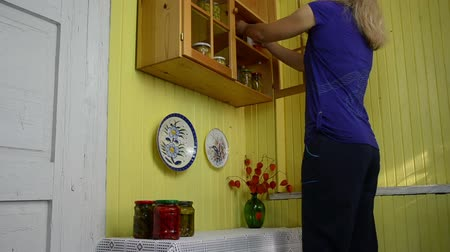 conservado : housewife prioritizes jars the wooden cupboard shelves with canned vegetables for winter use