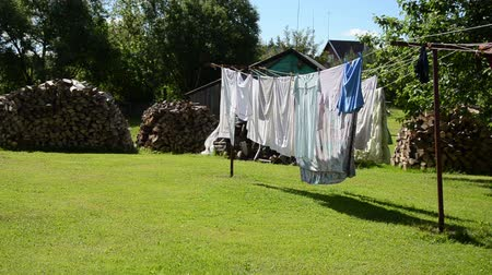 prendedor de roupa : laundry hang dry on outdoor rope move in wind and firewood wood stacked in village yard. Stock Footage
