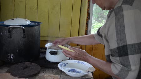 cooking pots : Old senior woman cook put potato dumplings cepelinas with meat in boiling pot water on rural kichen stove.