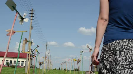 луг : girl woman with skirt billowing in wind goes between spin handmade pinwheel windmills avenue in meadow grass. Стоковые видеозаписи