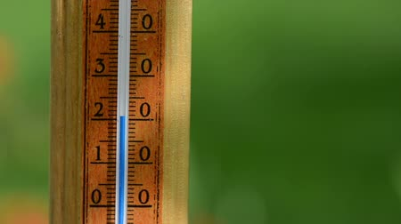 temp : Closeup of fast rising temperature on wooden thermometer scale exceed 30 degree. Celsius measurement unit.