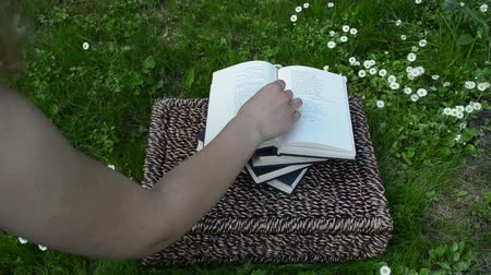 znalost : Woman hand put little daisy flower as marker between book pages in garden. Dostupné videozáznamy