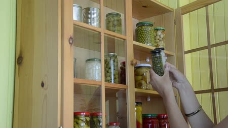 conservado : girl from a wooden cupboards with glass takes two oblong jars with capers and garlic