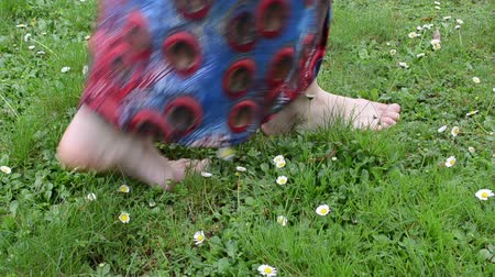 çim : bare foot woman with dress walk through meadow full of small daisy flowers.