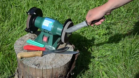 bıçak : Knife sharpening with special grinder tool on outdoor wooden log betwqeen grass. Stok Video