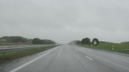 rainy : cars drive on highway road and rain falling. Front automobile window windscreen view and wipers work. Bad weather conditions in autumn. Stock Footage