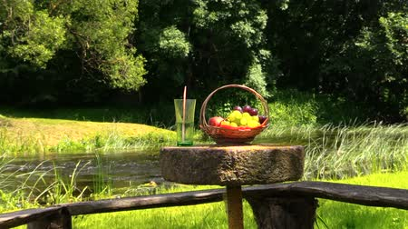 calcário : Wicker basket with grape and peach fruits and glass with champagne cider on millstone table near river. Picnic in nature. Zoom out shot on Canon XA25. Full HD 1080p. Progressive scan 25fps. Tripod. Stock Footage