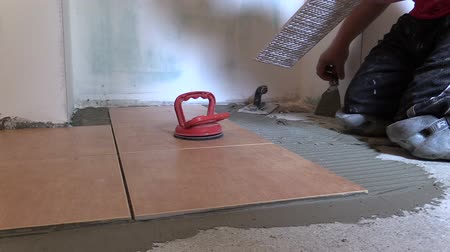 ceramika : Construction worker place floor tiles. Home renovation, improvement. Right side sliding shot on Canon XA25. Full HD 1080p. Progressive scan 25fps. Dolly camera movement.