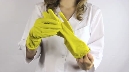 luva : Woman in white robe smock put on yellow rubber gloves on her hands. Full HD 1080p. Progressive scan 25fps. Tripod.